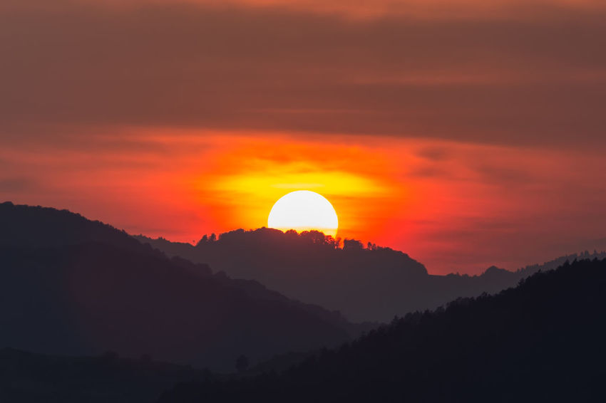 Bright Morning Sunlight Cloud - Sky Colorful Dawn Dusk Environment Evening Forest Horizon Idyllic Landscape Majestic Mountain Peak Mountain Range Nature Orange Color Outdoors Scenics - Nature Silhouette Sky Summer Sunrise Sunset