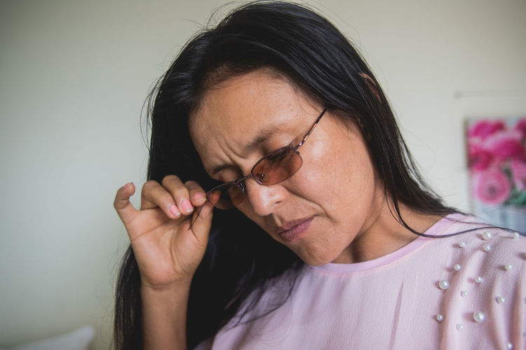Portrait of woman wearing eyeglasses at home