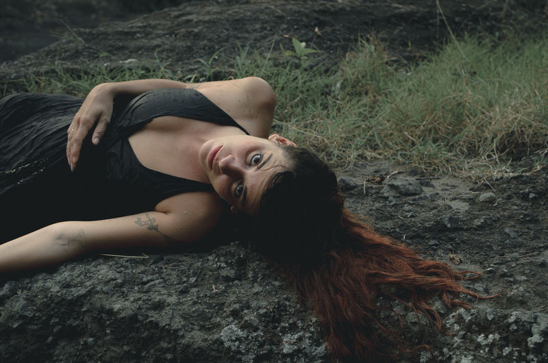 Portrait of woman lying down in forest