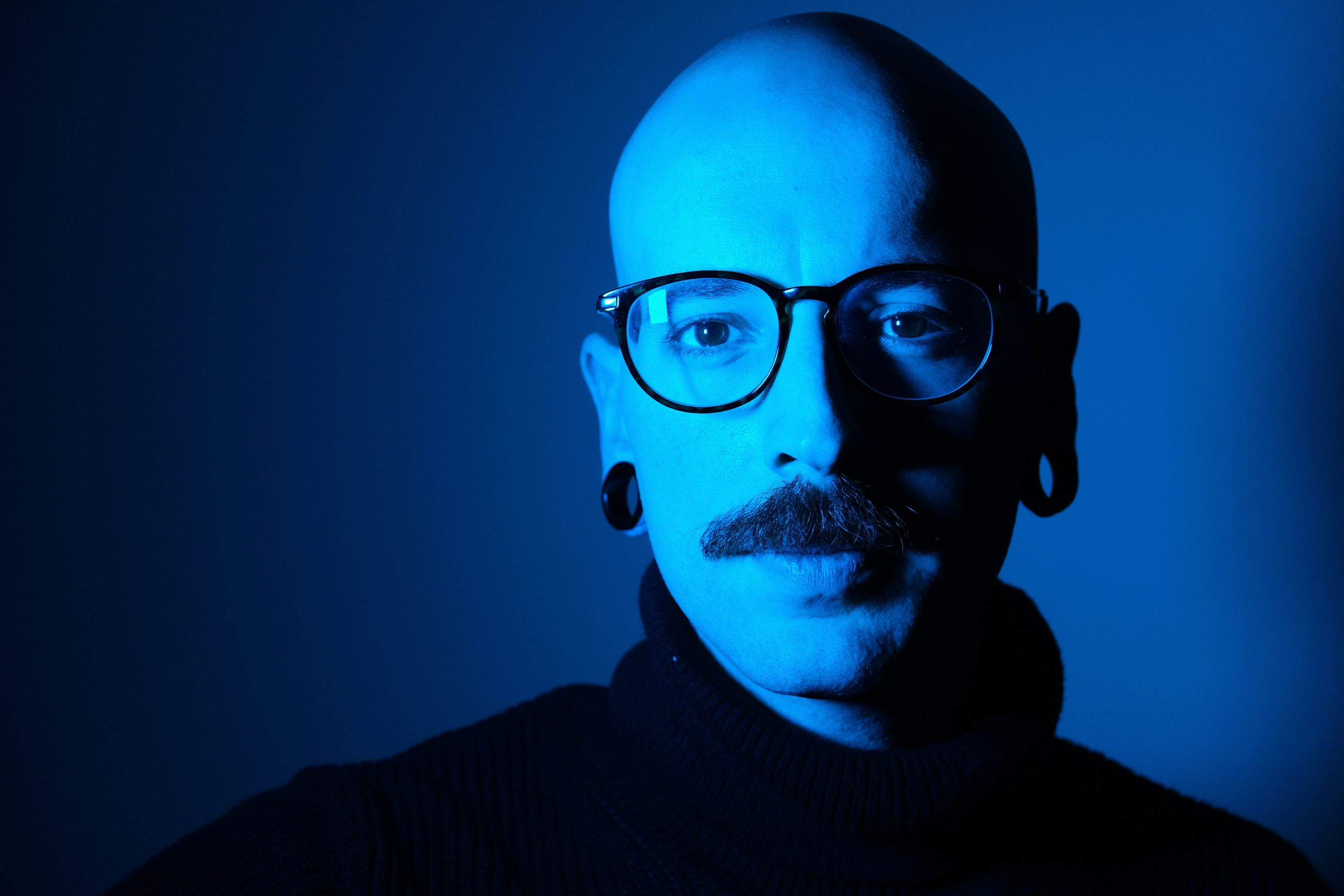 headshot, portrait, one person, blue, front view, glasses, real people, men, lifestyles, eyeglasses, young men, young adult, mid adult, indoors, leisure activity, illuminated, mid adult men, sunglasses, males, human face, contemplation, blue background