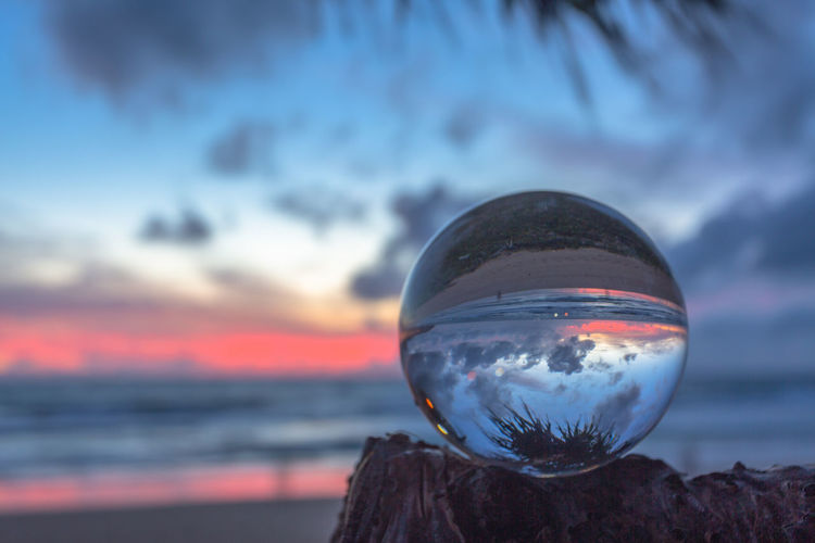 Close-up of crystal ball on rock against sea during sunset