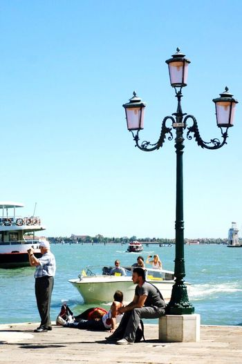 Street Light Transportation Clear Sky Nautical Vessel Water Sitting Lifestyles Mode Of Transport Person Boat Leisure Activity Blue River Ship Relaxation Travel Destinations Casual Clothing Day Lamp Post