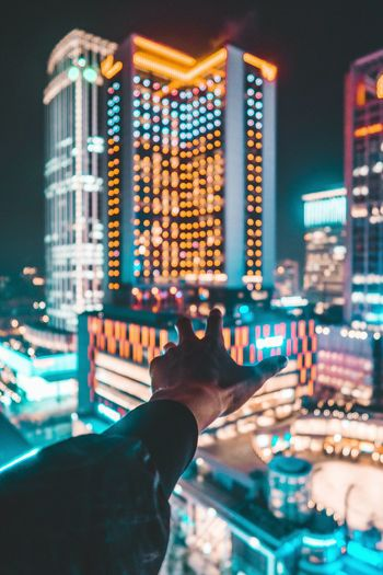 Close-up of hand on illuminated cityscape at night