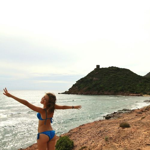 Happy Woman In Bikini Standing At Seaside Against Sky
