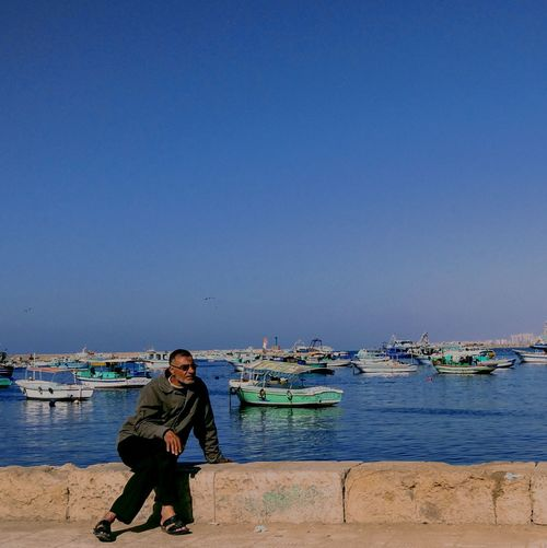 Mature man sitting on retaining wall by sea against clear blue sky