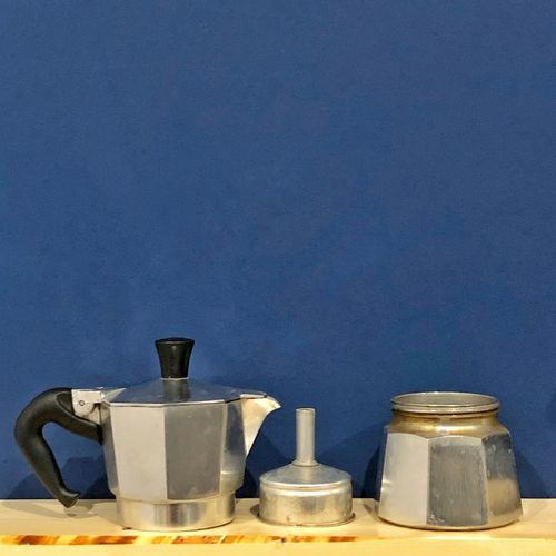 Espresso cooker on a shelf Espresso Break Espresso Machine Espresso Maker Blue Container No People Still Life Indoors  Group Of Objects Wall - Building Feature Close-up Metal Blue Background Colored Background Food And Drink Medium Group Of Objects Textured  Silver Colored Side By Side
