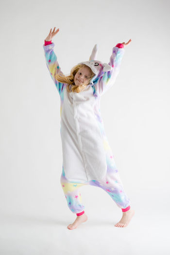 Portrait of happy girl with arms raised dancing against white background