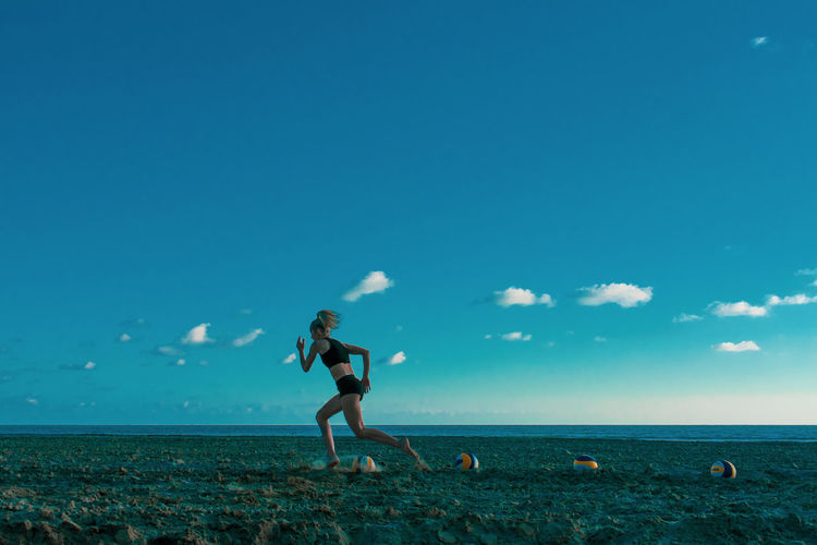 Side view of young woman running while exercising at beach against blue sky