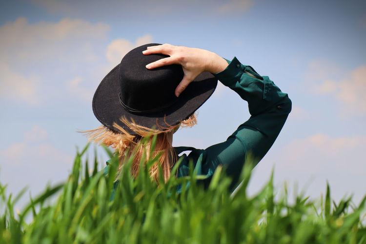 Woman wearing hat on field against sky