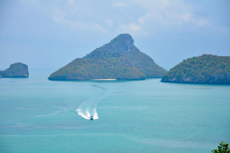 Seascape of islands in the tropical ocean with moving spped boat on the surface of sea in sunny day.