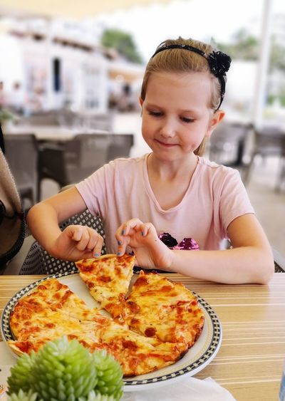 Girl eating pizza on table at restaurant