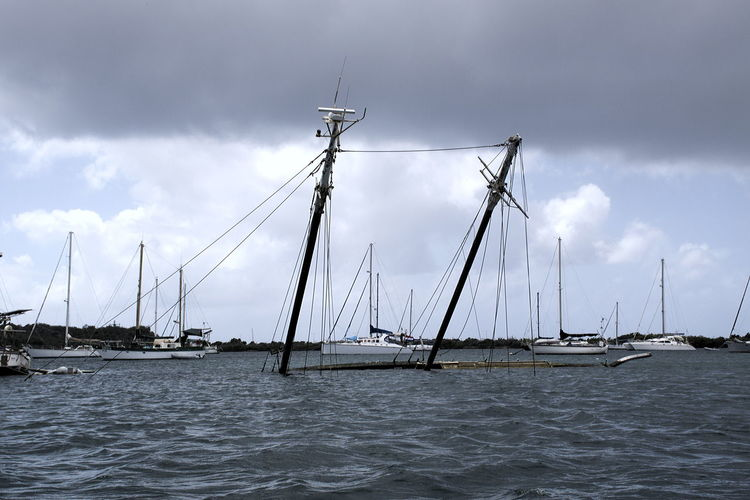 Only masts remain to be seen of a sailing yacht in Curaçao, Spanish Water Beauty In Nature Cloud - Sky Clouds And Sky Day Idyllic Mast Mode Of Transport Nature Nautical Vessel No People Outdoors Sailboat Scenics Sea Sky Sunken Boat Sunken Yacht Tranquil Scene Tranquility Transportation Water Waterfront