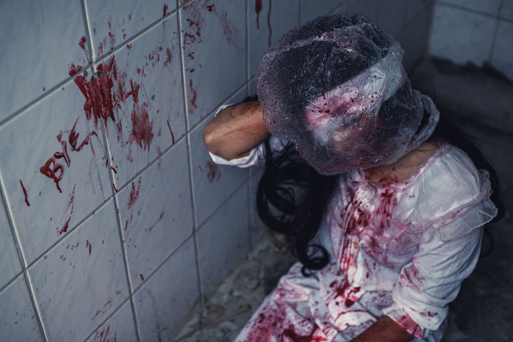 High angle view of young woman with plastic on head kneeling by wall