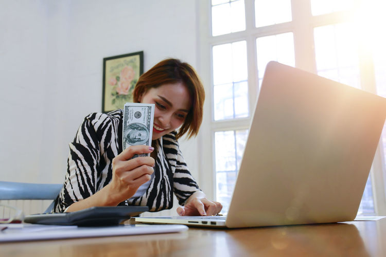 Smiling businesswoman using laptop while holding money at office desk