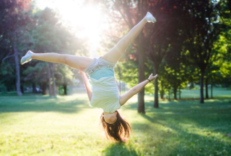 Full Length Of Young Woman Jumping In Park