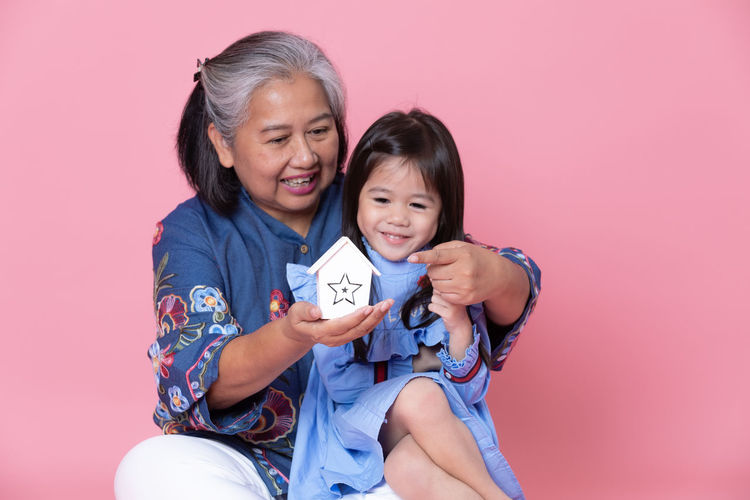 Smiling grandmother showing model home to granddaughter against pink background
