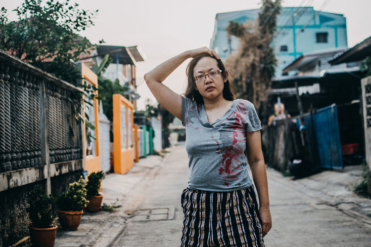 Young woman standing on street against buildings in city