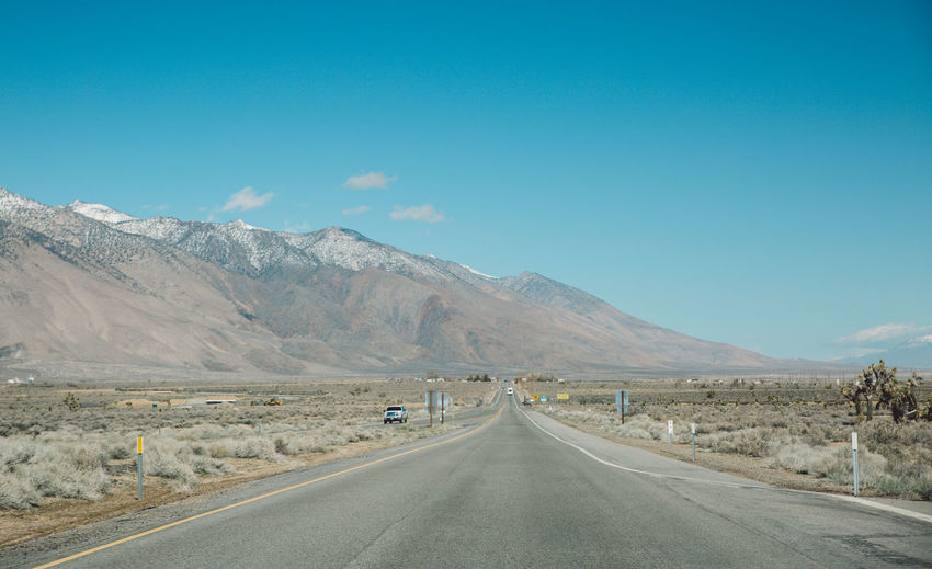 Empty road by mountain against blue sky