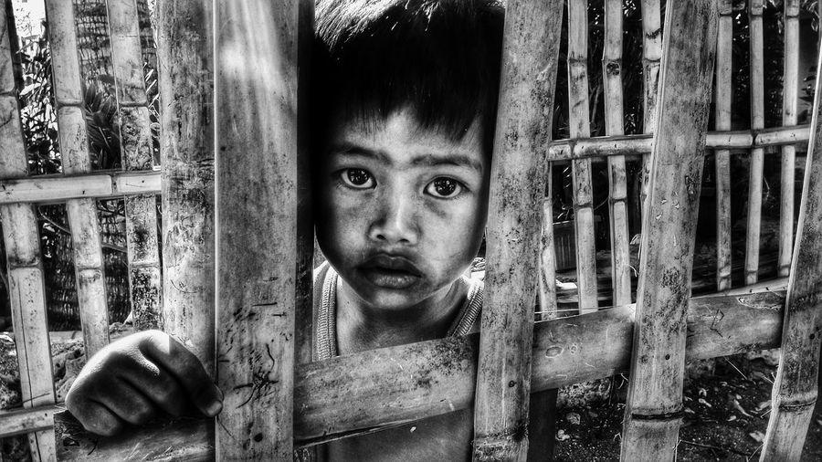 Close-up portrait of homeless boy seen through bamboo fence
