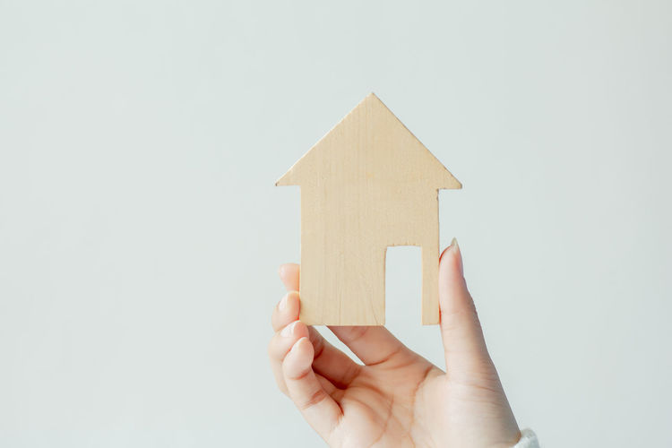 Woman holding model home against gray background