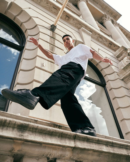 Low angle view of man standing by windows of building
