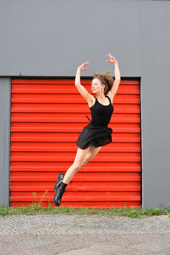 Full length of woman jumping against wall