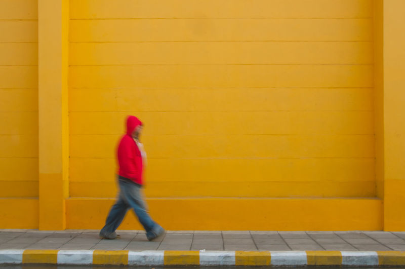 Red hooded man walking on yellow line Blurred Motion Color Lifestyles Lines Moody Pattern Red Relax Street Streetphotography Trip Walking Yellow