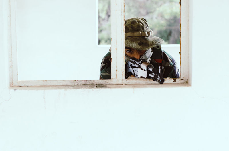 Special forces soldier holding rifle gun aim window white frame cover Window One Person Copy Space Indoors  Day Adult Occupation Real People Mid Adult Waist Up Men Wood - Material Headshot Holding Reflection Young Adult Helmet Portrait Airsoft Sniper Trooper Soldier Army Army Soldier Special Forces Aim Aiming Camouflage Clothing Camouflage Hat AK 47 Gun
