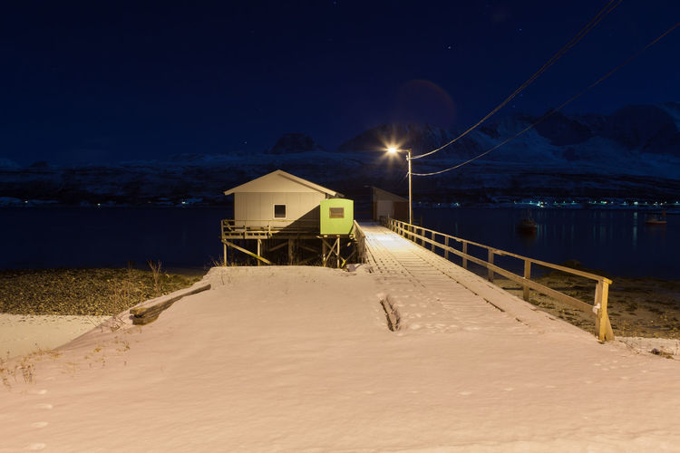 Snow covered pier by lake against sky at night