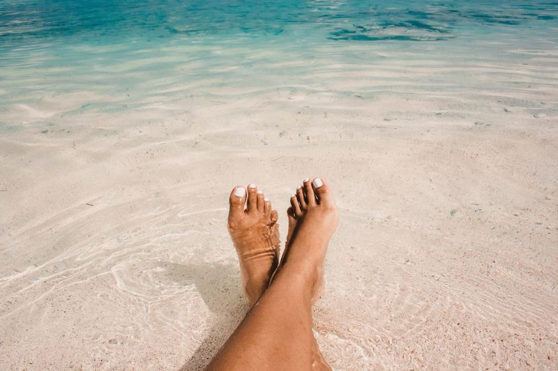 Low section of woman relaxing in sea