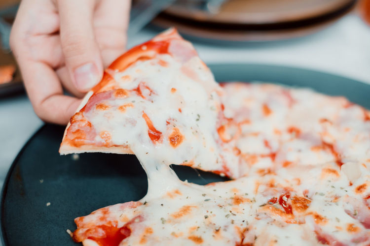 Close-up of hand holding pizza in plate