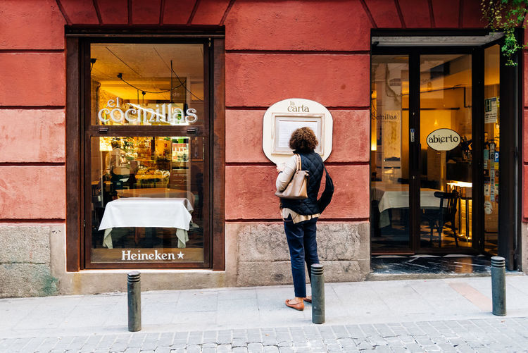 Woman looking the menu in retro restaurant in Malasaña Quarter in Madrid City European  Madrid Malasaña Menu Retro SPAIN Woman People Quarter  Resataurant Storefront Trendy Vintage