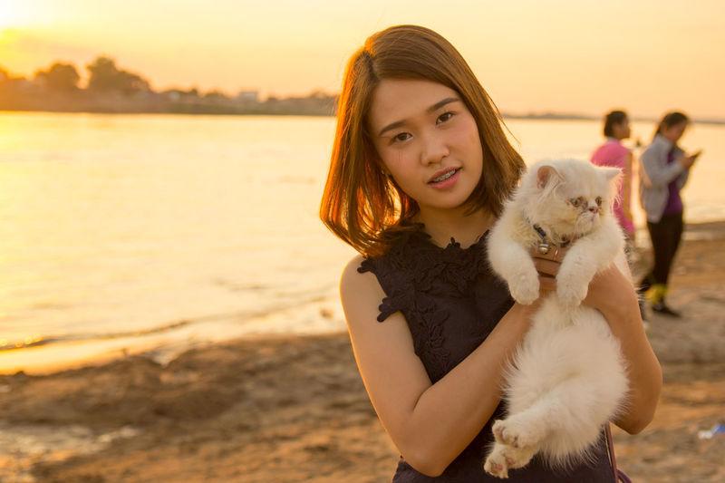 A girl on the beach with her cute cat Moments Of Happiness Girl Portrait Happy Feeling Happy Emotion Emotional Photography Funny Happy Face ForTheLoveOfPhotography Sunset Sunset_collection Lao Girl Sky Leisure Activity Young Women Water Focus On Foreground Young Adult Looking At Camera Waist Up One Person Real People Nature Women Lifestyles Land Beauty Standing Beautiful Woman Teenager Hairstyle Outdoors EyeEmNewHere EyeEm Best Shots EyeEm Nature Lover EyeEm Selects