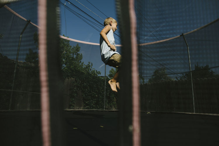 Low angle view of man jumping on fence