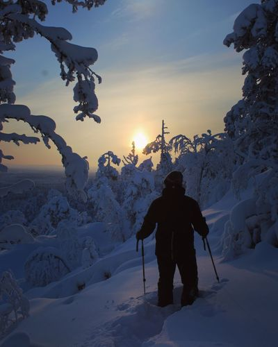 Rear view of man skiing on snow covered mountain against sky