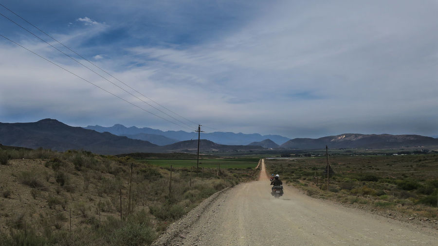 Couple on motorcycle traveling along open dirt road Adventure Dirt Road Explore Journey Land Vehicle Landscape Mode Of Transport Motorbike Motorcycle Mountain Mountain Range Open Road Outdoors Riding Road Sky Transportation Travel Vanishing Point Let's Go. Together.