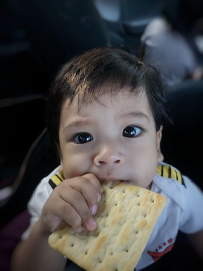 Portrait Of Cute Baby Boy Eating Cracker At Home
