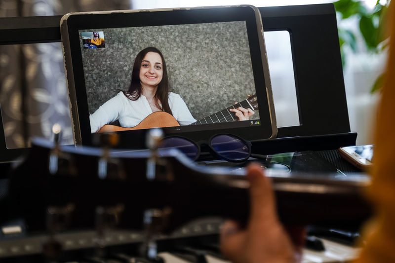 Cropped hand of woman playing piano while video conferencing over digital tablet at home