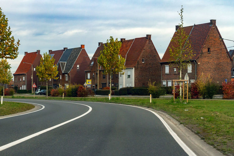 Road amidst houses and buildings against sky