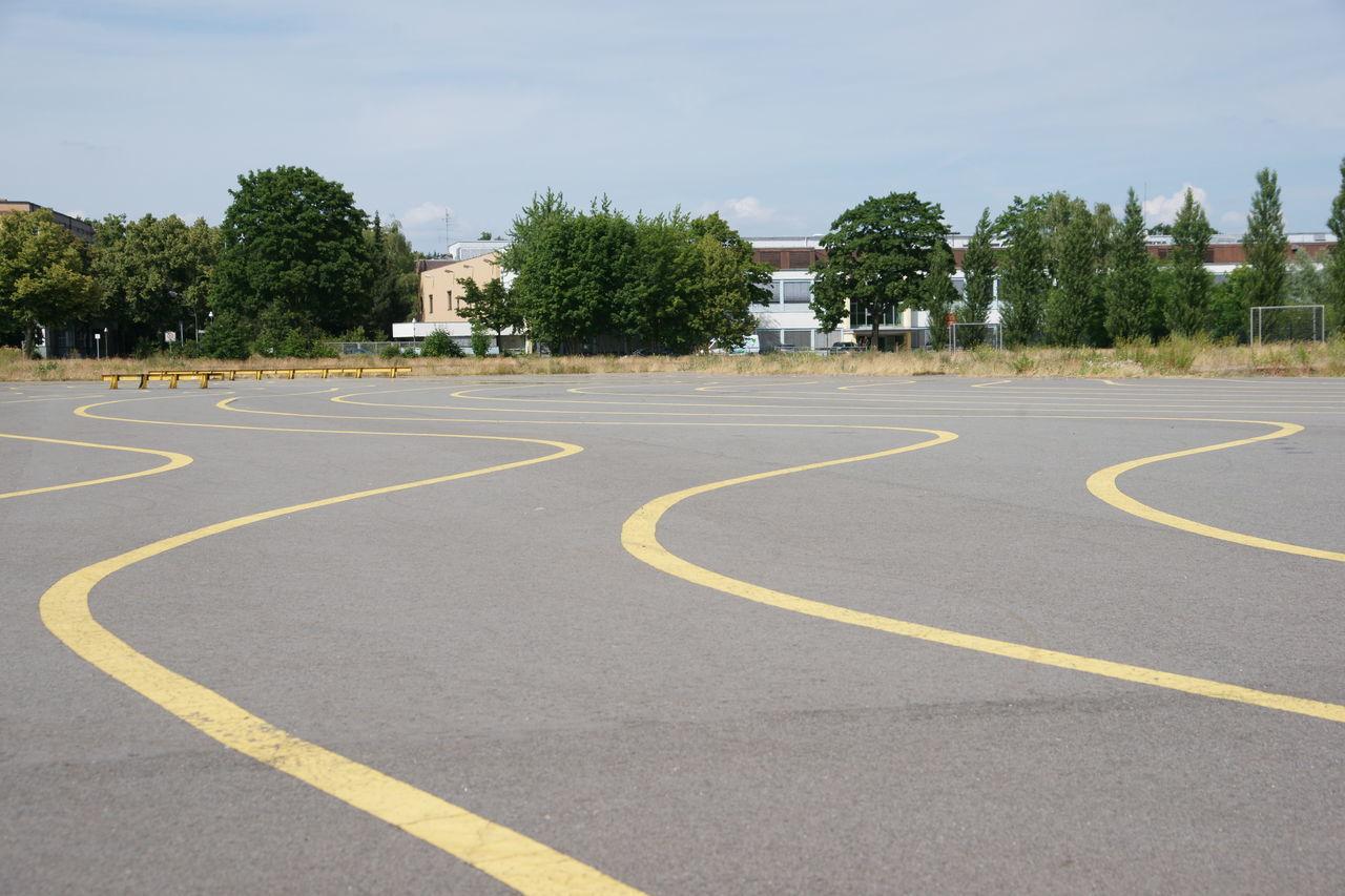 Wave Pattern Road Marking In Parking Lot Against Sky