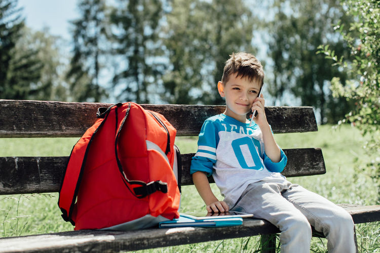 Schoolboy taking a break on a bench and making a phone call. 6 Years Alone Cellphone Copy Space Green Horizontal Mobile Phone Red School Bag Sitting Back To School Banch Boy Break Caucasian Child Day One Person Phone Call Play Real People Resting School Technology Young Student