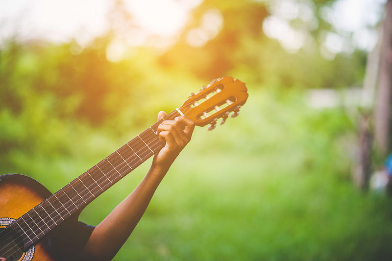 Cropped hand of person playing guitar over field