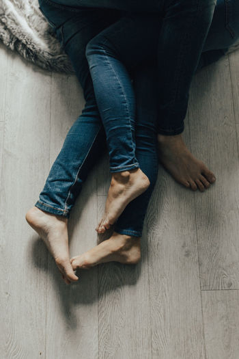 Low section of couple hugging on hardwood floor