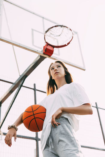 Portrait of a thoughtful girl basketball player with a ball in her hands. basketball, sports