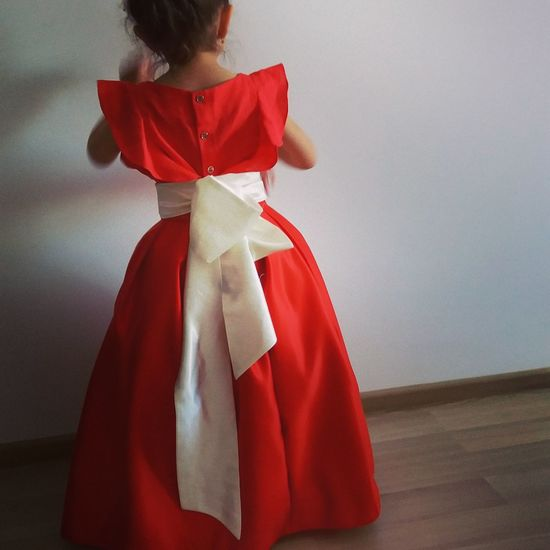 Rear view of girl standing against wall