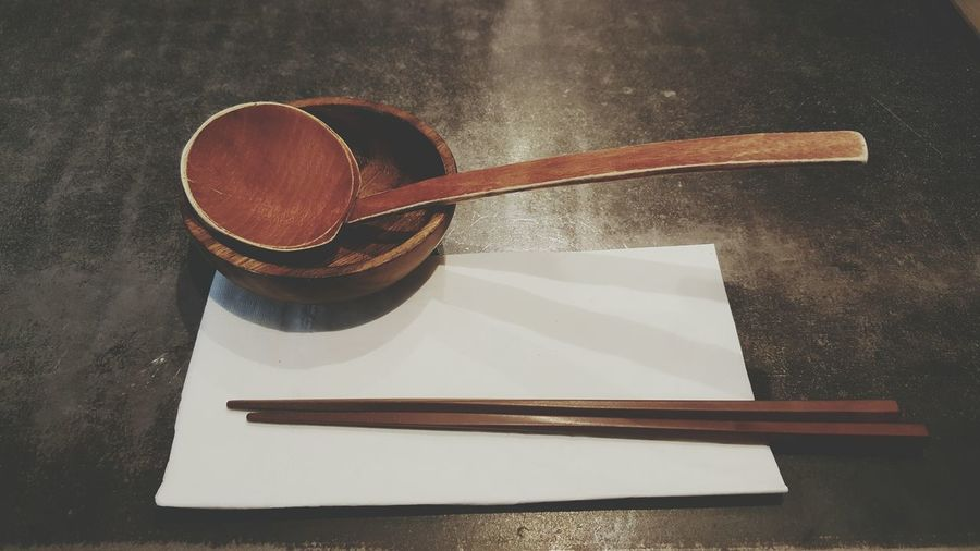 High Angle View Of Chopsticks And Wooden Spoon On Table