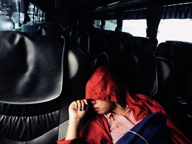 Women sleeping on bus . Real People One Person Lifestyles Sitting Leisure Activity Vehicle Interior Indoors  Headshot Portrait Red Women Clothing Transportation Mode Of Transportation Unrecognizable Person Front View Adult Covering Obscured Face
