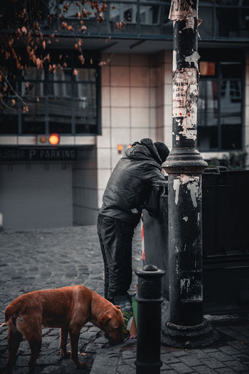 Man standing by street in city