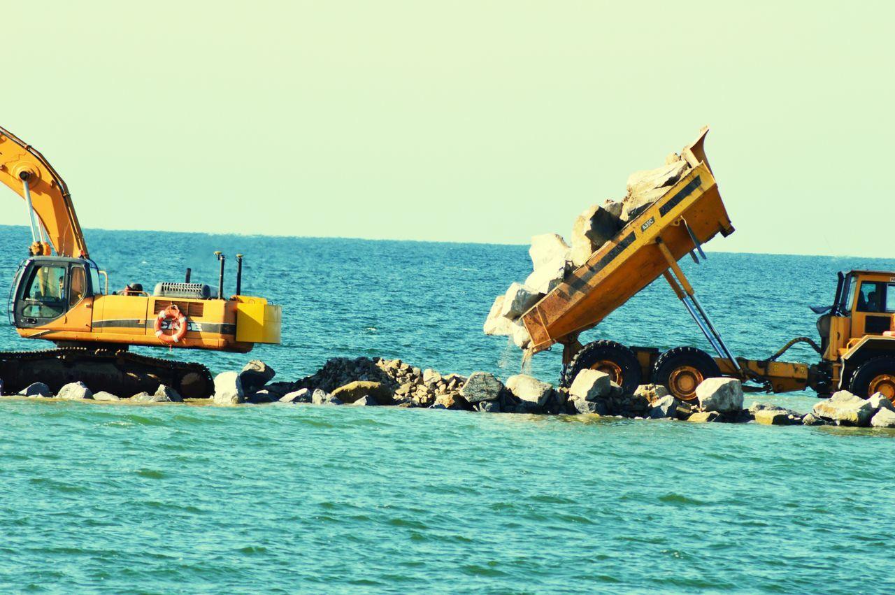 Truck Dumping Rocks On Walkway Amidst Sea