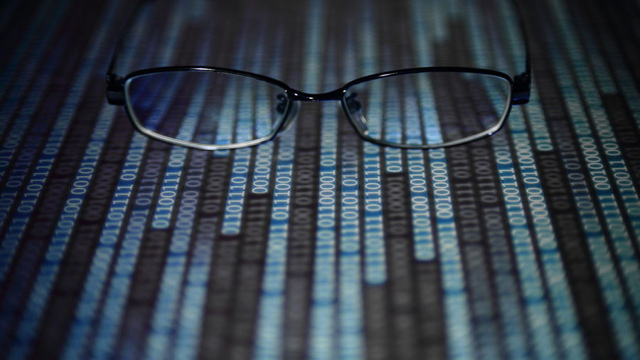 Close-up of eyeglasses on binary codes